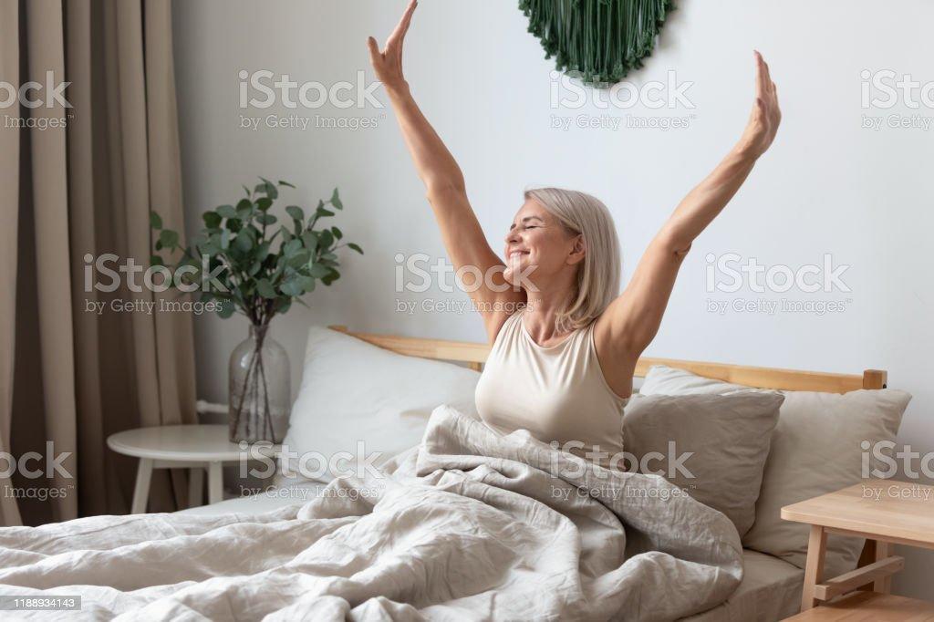 Gelukkig volwassen vrouw stretching in bed wakker gelukkig concept - Royalty-free Alleen volwassenen Stockfoto