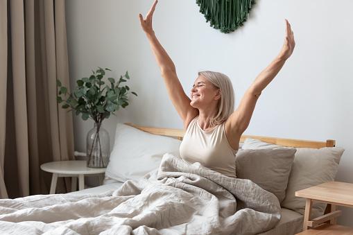 Gelukkig Volwassen Vrouw Stretching In Bed Wakker Gelukkig Concept Stockfoto en meer beelden van Alleen volwassenen