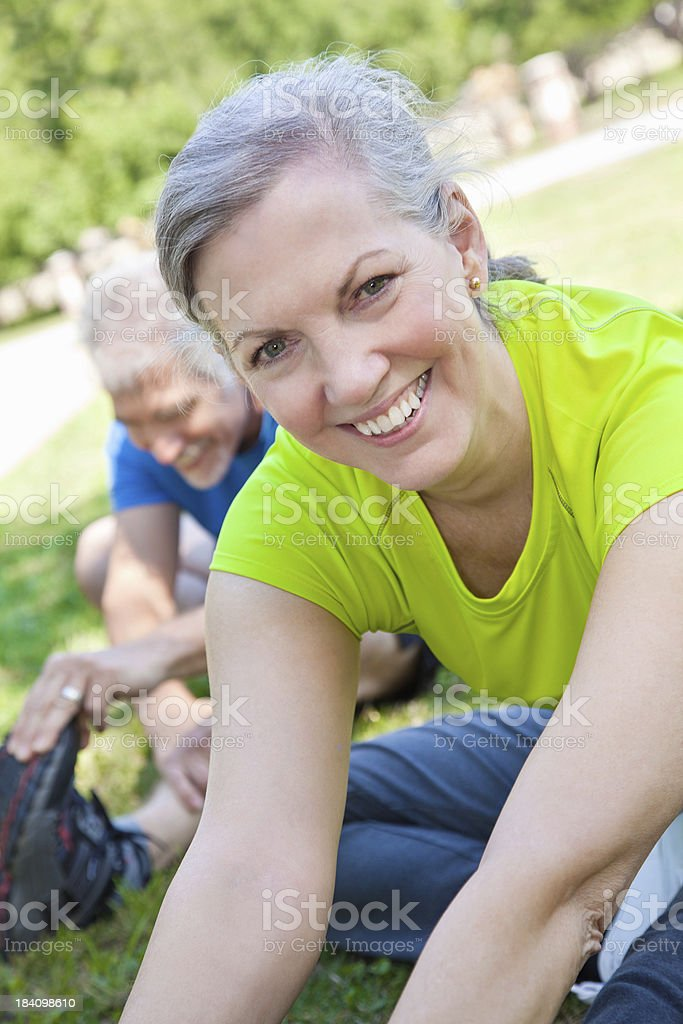 Happy Mature Woman Stretching Outside With Partner royalty-free stock photo