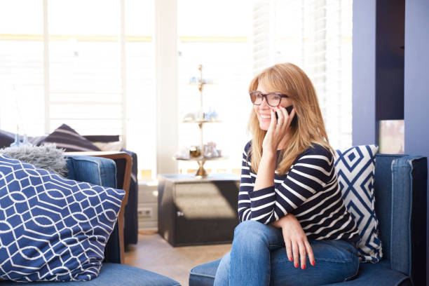 Cтоковое фото Happy mature woman talking with somebody on her cell phone while sitting on sofa