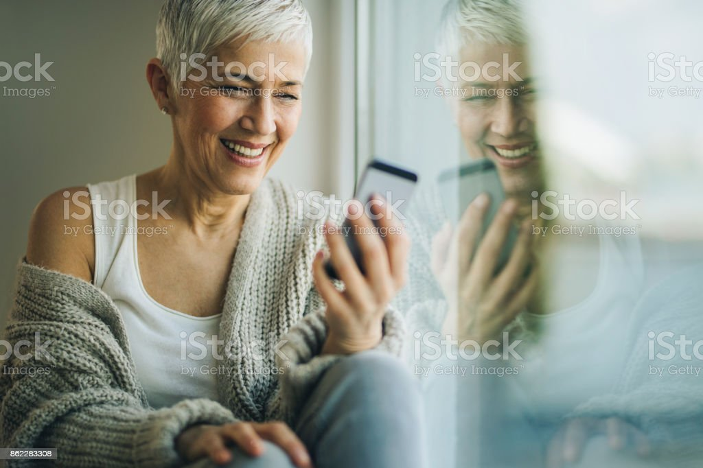 Happy mature woman text messaging on mobile phone by the window. stock photo