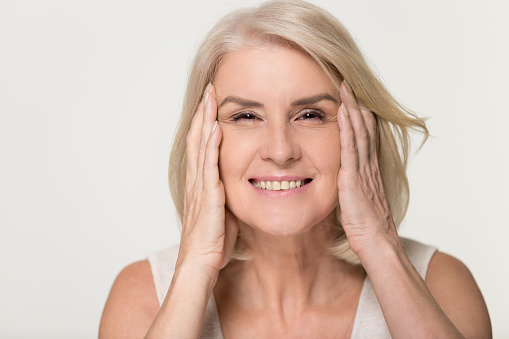 istock Happy mature woman touching face isolated, anti aging beauty concept 1135587125