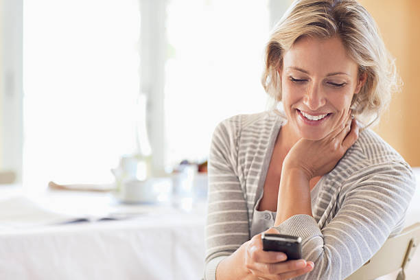 Happy mature woman using cell phone at home stock photo