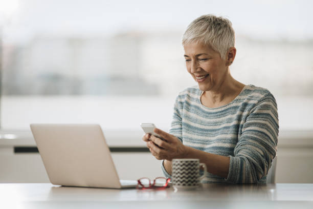 happy mature woman using cell phone while working on laptop at home. - older woman phone stock photos and pictures