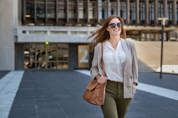 femme mature heureuse marchant en toute confiance - mode bureau photos et images de collection