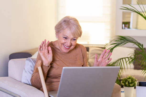 Happy mature woman waving to someone while having a video call over laptop at home. Gray-haired senior woman waving hand in front of laptop while having video call with her family members. Happy mature woman waving to someone while having a video call over laptop at home. Gray-haired senior woman waving hand in front of laptop while having video call with her family members. zoom stock pictures, royalty-free photos & images
