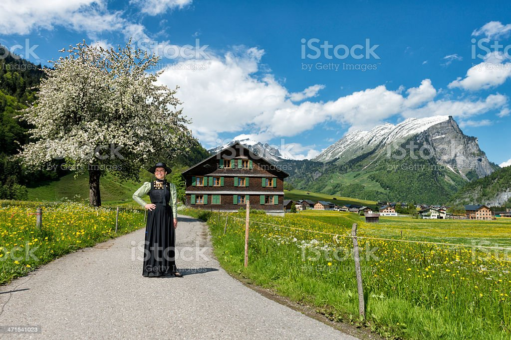 happy mature woman wearing dirndl in beautiful landscape stock photo