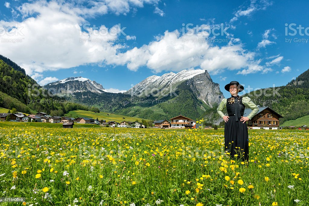 happy mature woman wearing dirndl standing in flower meadow stock photo