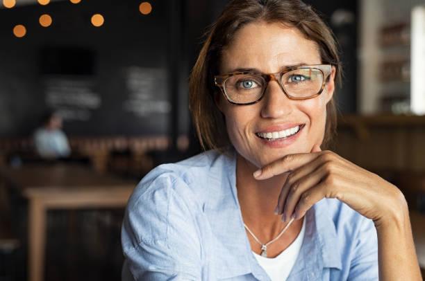 happy mature woman wearing eyeglasses - mano sul mento foto e immagini stock