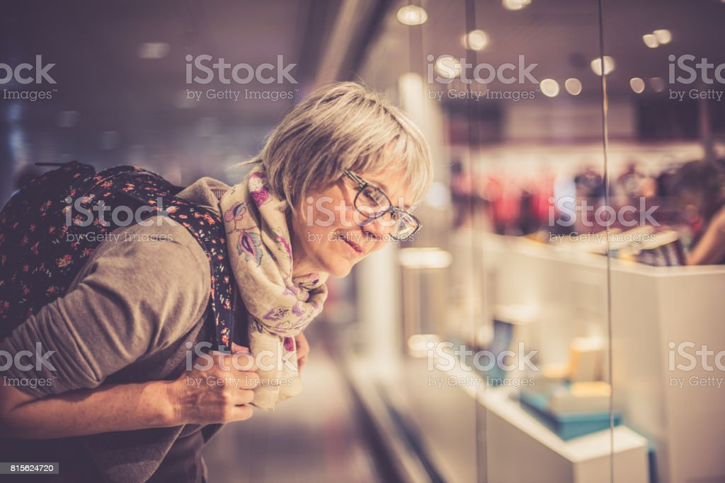 Happy Mature Woman Window Shopping while Waiting her Flight at the Airport Terminal, Germany stock photo