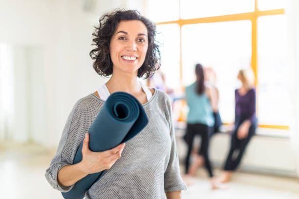 Happy mature woman with a yoga mat in health club stock photo