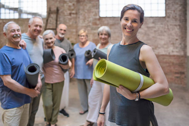 Happy mature woman with a yoga mat in health club Happy mature woman with a yoga mat in health club yoga instructor stock pictures, royalty-free photos & images