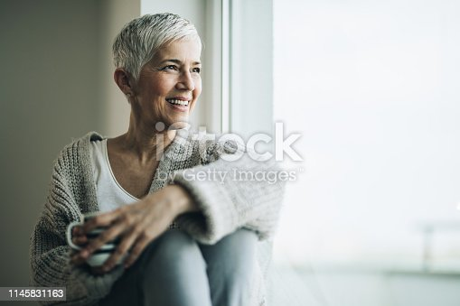 Happy senior woman relaxing by the window during coffee time. Copy space.