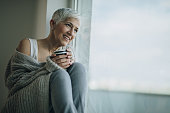 istock Happy mature woman with coffee cup relaxing by the window. 849173930