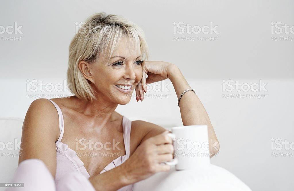 Happy mature woman with coffee cup sitting on couch royalty-free stock photo