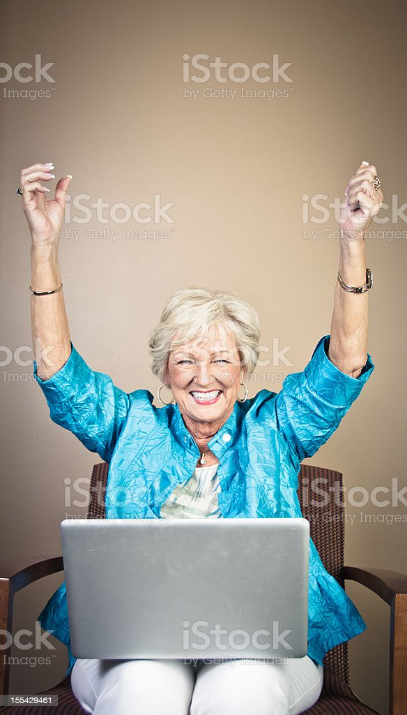 Happy Mature Woman With Laptop stock photo