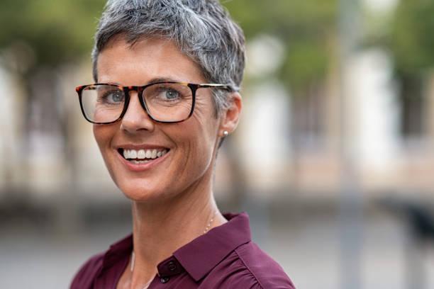 gelukkige rijpe vrouw met bril - mid volwassen vrouw stockfoto's en -beelden