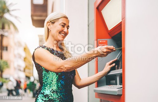 945598452istockphoto Happy mature woman withdraw money from bank cash machine with debit card - Senior female doing payment with credit card in ATM - Concept of business, banking account and lifestyle people 1131559546