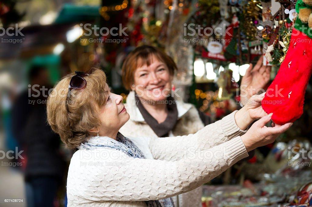 Happy mature women purchasing Christmas decorations stock photo