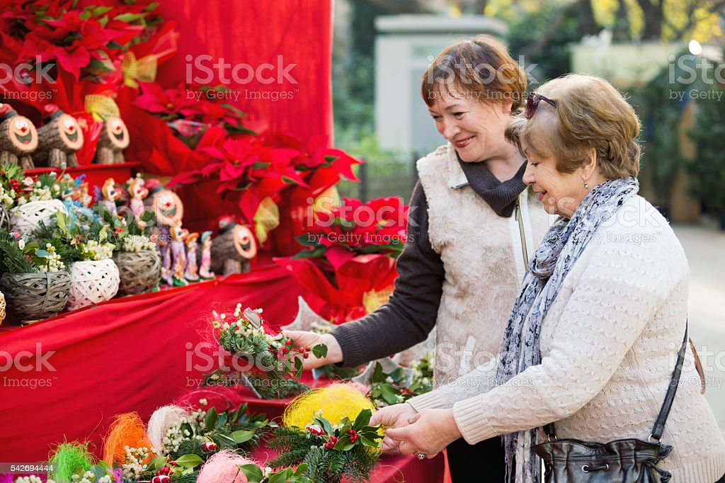 Happy mature women selecting floral compositions stock photo