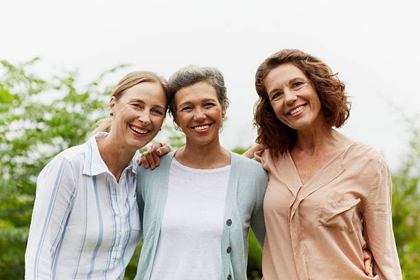 happy mature women standing in park - three people stock photos and pictures