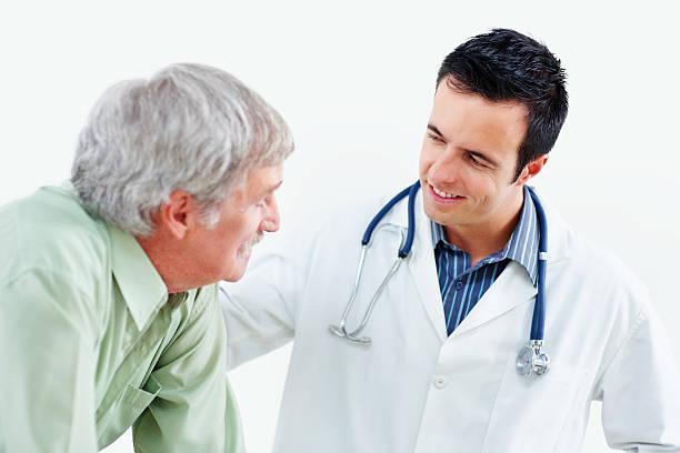 happy medical doctor comforting senior patient against white - hospital studio bildbanksfoton och bilder