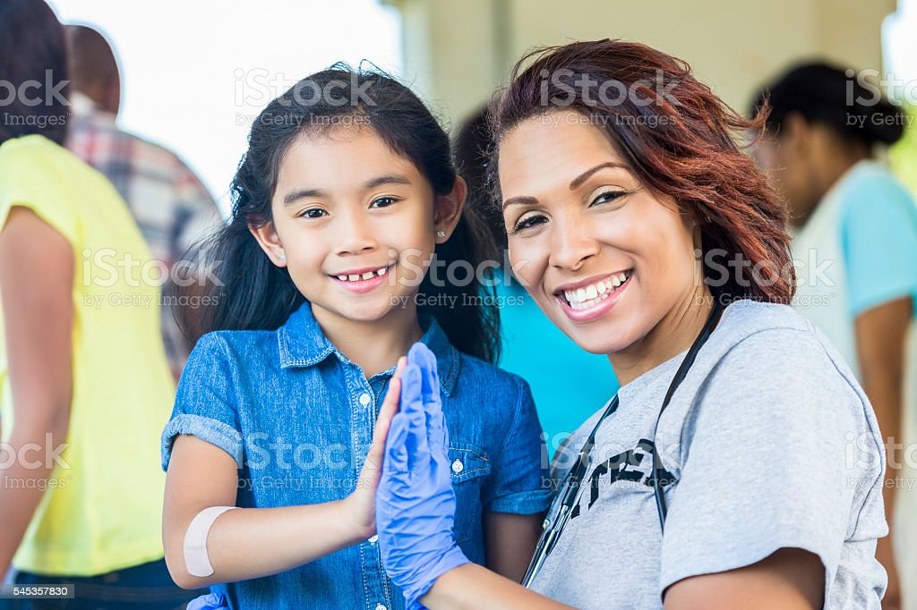 Happy medical volunteer and little girl high fiving stock photo