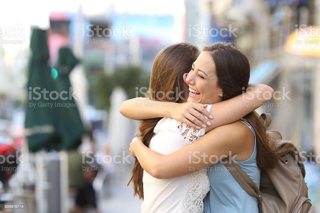 Happy meeting of friends hugging stock photo