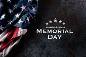 Happy Memorial Day. American flags with the text REMEMBER & HONOR against a black stone texture background. May 25.