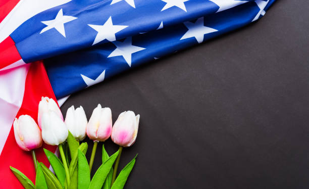 happy memorial day recuerde anteriormente, pero ahora rara vez llamado día de la decoración, bandera americana y una flor de tulipán sobre un fondo negro y espacio de copia, un día festivo federal en los estados unidos - memorial day fotografías e imágenes de stock