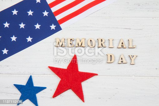 971061452istockphoto Happy Memorial Day. Stars and American flag on white wooden background 1137110136