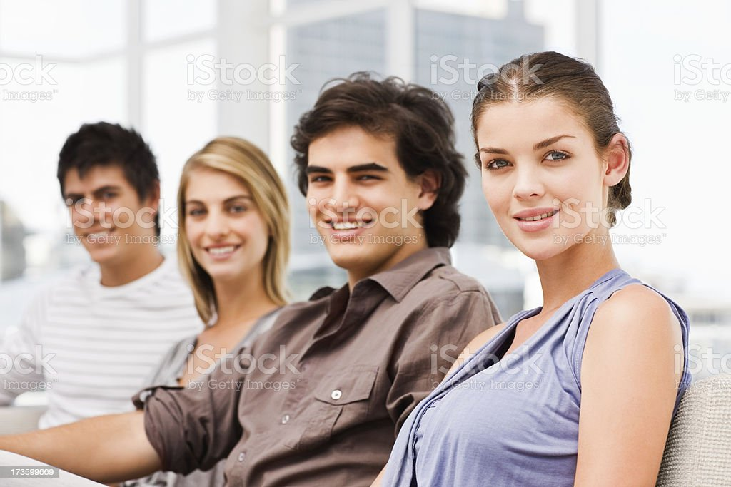 Happy men and women sitting together on couch royalty-free stock photo