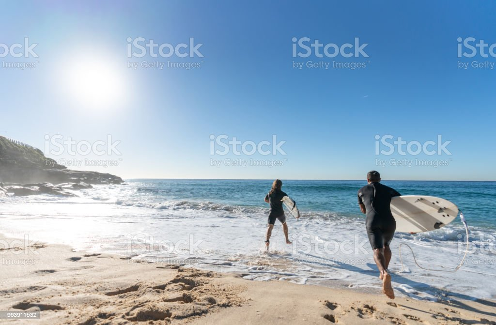 Happy men having fun surfing at the beach - Royalty-free Adult Stock Photo