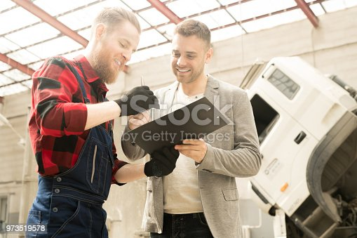 962888586 istock photo Happy Men In Auto Repair Service 973519578