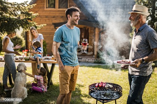 istock Happy men talking while preparing barbecue for his family in the backyard. 1096861888