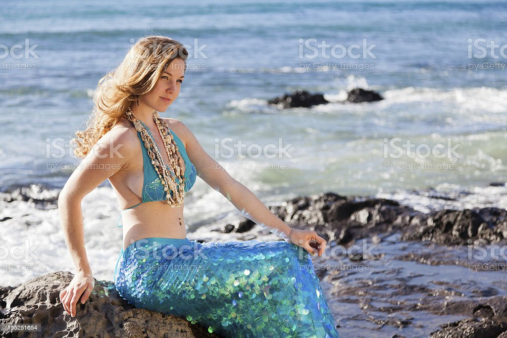 Happy Mermaid Sitting on a Rock in the Sun stock photo