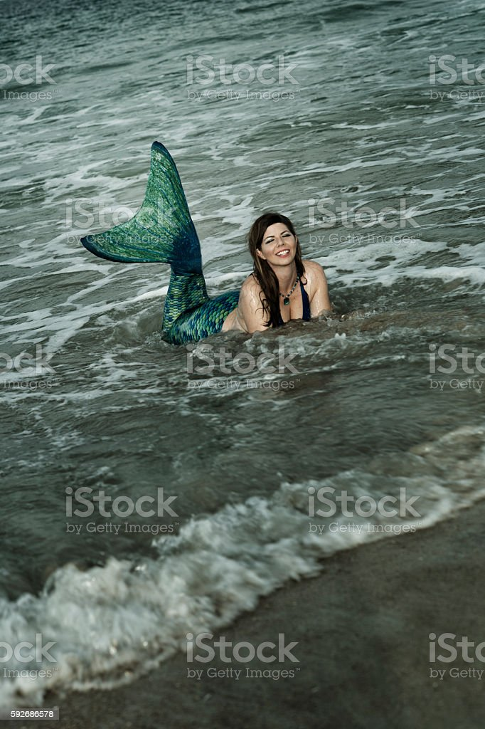 Happy mermaid with green tail in ocean stock photo