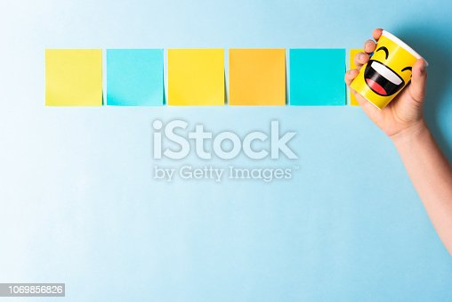 istock Happy message concept with five multicolored notes and a hand showing a emoticon smiling paper cup on blue background 1069856826