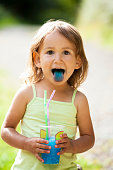 Funny portrait of happy messy little girl stikicng out blue tongue after enjoying flavoured ice