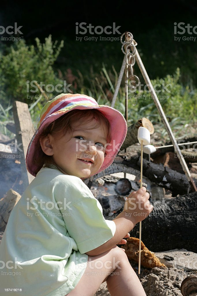 Happy messy little girl with marshmallow royalty-free stock photo