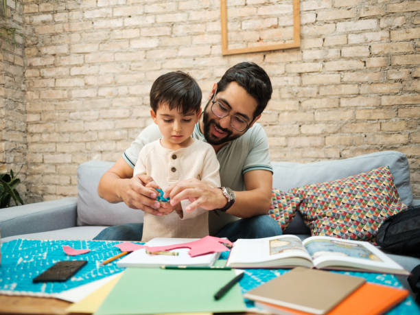 Happy mexican father helping little boy to use pair of scissors stock photo