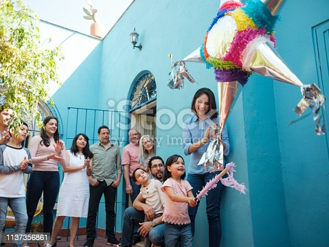A happy mexican girl hitting a piñata with a stick next to her mother and family standing in the background looking at her.