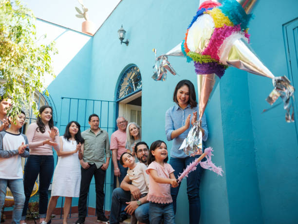 Happy mexican girl hitting piñata with stick and family looking A happy mexican girl hitting a piñata with a stick next to her mother and family standing in the background looking at her. mexican culture stock pictures, royalty-free photos & images