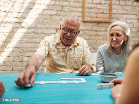 A cheerful Mexican grandpa laying out domino pieces on the table sitting next to his smiling wife.