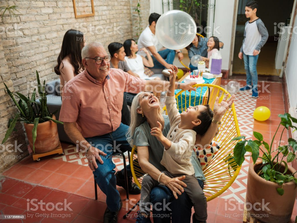 Happy mexican grandparents and grandson playing with balloon Happy mexican parents sitting with their grandson on chairs and playing with a balloon during a birthday celebration at home. Family Stock Photo