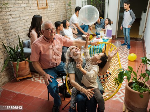 Happy mexican parents sitting with their grandson on chairs and playing with a balloon during a birthday celebration at home.