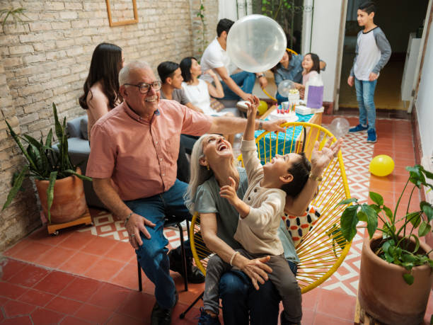 Happy mexican grandparents and grandson playing with balloon stock photo