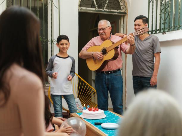 fröhlicher mexikanischer großvater, der gitarre spielt, vor der familie - gitarren geburtstagstorten stock-fotos und bilder