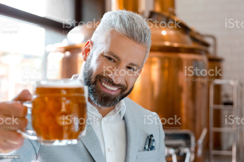 Happy microbrewery owner looking at beer mug Happy microbrewery owner looking at beer mug. Smiling businessman examining the beer quality. Adult Stock Photo