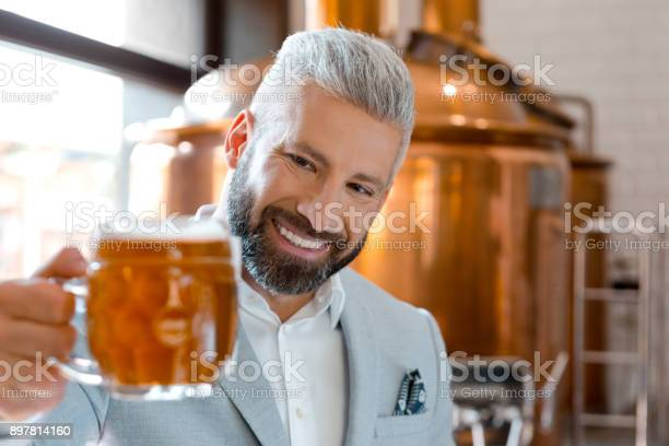 Happy Microbrewery Owner Looking At Beer Mug Stock Photo - Download Image Now